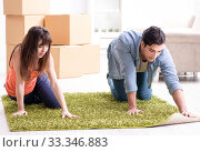 Young family rolling carpet at new apartment. Стоковое фото, фотограф Elnur / Фотобанк Лори