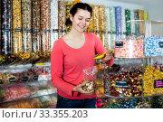 Купить «Woman posing to photographer picking different candies», фото № 33355203, снято 22 марта 2017 г. (c) Яков Филимонов / Фотобанк Лори