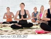 Купить «Girls practicing yoga in lotus position on beach», фото № 33355267, снято 22 мая 2017 г. (c) Яков Филимонов / Фотобанк Лори