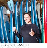 Adult woman standing next to paddle boards. Стоковое фото, фотограф Яков Филимонов / Фотобанк Лори