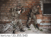 Купить «Two men in military camouflage vegetato uniforms with automatic assault rifles», фото № 33355543, снято 10 июля 2016 г. (c) katalinks / Фотобанк Лори