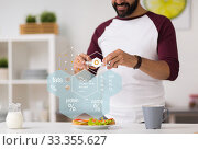 man with phone and food nutritional value chart. Стоковое фото, фотограф Syda Productions / Фотобанк Лори