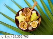 Купить «mix of exotic fruits in wooden plate with spoon», фото № 33355763, снято 16 ноября 2018 г. (c) Syda Productions / Фотобанк Лори
