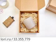 Купить «parcel with straw filler and mug at post office», фото № 33355779, снято 11 января 2019 г. (c) Syda Productions / Фотобанк Лори