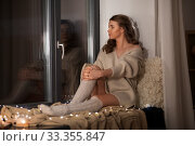 woman in pullover sitting on windowsill at home. Стоковое фото, фотограф Syda Productions / Фотобанк Лори