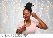 Купить «happy african american woman with red clown nose», фото № 33355991, снято 26 января 2020 г. (c) Syda Productions / Фотобанк Лори