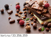 Купить «close up of different chocolates, candies and nuts», фото № 33356359, снято 1 февраля 2019 г. (c) Syda Productions / Фотобанк Лори