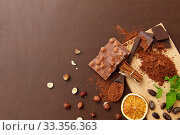 Купить «chocolate with hazelnuts, cocoa beans and powder», фото № 33356363, снято 1 февраля 2019 г. (c) Syda Productions / Фотобанк Лори