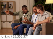 Купить «male friends watching tv and talking at home», фото № 33356371, снято 28 декабря 2019 г. (c) Syda Productions / Фотобанк Лори