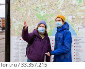 Купить «Tallinn, Estonia - MAR 07, 2020: Two tourists in medical face masks are standing at big city map», фото № 33357215, снято 7 марта 2020 г. (c) Юлия Кузнецова / Фотобанк Лори