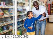 Smiling man and boy reading shopping list. Стоковое фото, фотограф Яков Филимонов / Фотобанк Лори