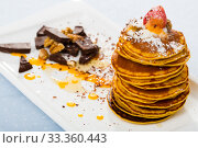 Pancakes served with honey, fruit, chocolate and whipped cream at plate. Стоковое фото, фотограф Яков Филимонов / Фотобанк Лори