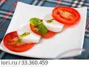 Купить «Salad caprese with tomatoes, mozzarella cheese and herbs», фото № 33360459, снято 11 июля 2020 г. (c) Яков Филимонов / Фотобанк Лори