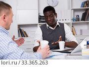 Купить «Smiling businessman with partner in coffee break in office», фото № 33365263, снято 26 февраля 2018 г. (c) Яков Филимонов / Фотобанк Лори