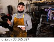 Купить «Proffessional young man engineer taking notes in notebook», фото № 33365327, снято 5 апреля 2020 г. (c) Яков Филимонов / Фотобанк Лори