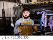 Купить «Worker with metal beams during work in workshop», фото № 33365335, снято 5 апреля 2020 г. (c) Яков Филимонов / Фотобанк Лори
