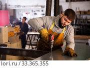 Купить «Workman drilling metal parts with hand drill», фото № 33365355, снято 28 мая 2020 г. (c) Яков Филимонов / Фотобанк Лори