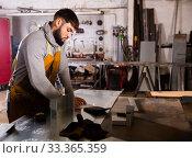 Купить «Foreman measures part and takes notes on paper», фото № 33365359, снято 26 мая 2020 г. (c) Яков Филимонов / Фотобанк Лори