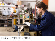 Купить «Female worker controls the size of a metal profile pipe», фото № 33365383, снято 4 февраля 2020 г. (c) Яков Филимонов / Фотобанк Лори