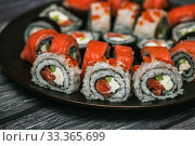 Купить «Various kinds of sushi served on dark plate macro», фото № 33365699, снято 11 марта 2020 г. (c) katalinks / Фотобанк Лори