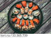 Купить «Various kinds of sushi served on dark plate macro», фото № 33365739, снято 11 марта 2020 г. (c) katalinks / Фотобанк Лори