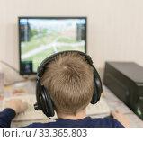 Купить «Ребёнок играет в компьютерную игру, вид сзади», фото № 33365803, снято 25 февраля 2020 г. (c) Игорь Тарасов / Фотобанк Лори