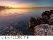 Купить «Calm beautiful evening seascape, in the foreground huge stones», фото № 33366119, снято 17 февраля 2020 г. (c) Иванов Алексей / Фотобанк Лори