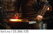Купить «Blacksmith working in the workshop - man heating up the longer piece of metal in the furnace and hitting it with a hammer», видеоролик № 33366135, снято 5 июня 2020 г. (c) Константин Шишкин / Фотобанк Лори