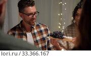 happy friends having christmas dinner at home. Стоковое видео, видеограф Syda Productions / Фотобанк Лори