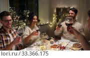 Купить «happy friends drinking red wine at christmas party», видеоролик № 33366175, снято 9 февраля 2020 г. (c) Syda Productions / Фотобанк Лори