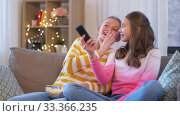 Купить «teenage girls eating popcorn watching tv at home», видеоролик № 33366235, снято 18 января 2020 г. (c) Syda Productions / Фотобанк Лори