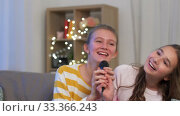 Купить «teenage girls with microphone singing at home», видеоролик № 33366243, снято 18 января 2020 г. (c) Syda Productions / Фотобанк Лори