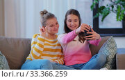 Купить «happy girls taking selfie with smartphone at home», видеоролик № 33366259, снято 18 января 2020 г. (c) Syda Productions / Фотобанк Лори