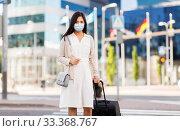 Купить «asian woman with travel bag in protective mask», фото № 33368767, снято 13 июля 2019 г. (c) Syda Productions / Фотобанк Лори