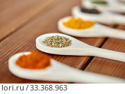 Купить «spoons with different spices on wooden table», фото № 33368963, снято 6 сентября 2018 г. (c) Syda Productions / Фотобанк Лори