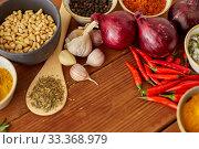 Купить «spices, onion, garlic, pine nuts and chili peppers», фото № 33368979, снято 6 сентября 2018 г. (c) Syda Productions / Фотобанк Лори
