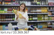 Portrait of young woman searching oil for cooking during shopping in store. Стоковое видео, видеограф Яков Филимонов / Фотобанк Лори