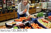Купить «Focused middle aged woman shopping in organic food store, choosing fresh vegetables», видеоролик № 33369375, снято 31 марта 2020 г. (c) Яков Филимонов / Фотобанк Лори