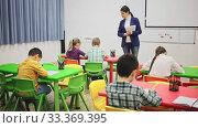Купить «Assiduous school kids with pens and notebooks studying in classroom with female teacher», видеоролик № 33369395, снято 26 марта 2020 г. (c) Яков Филимонов / Фотобанк Лори