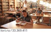 Купить «Schoolboys and girls preparing for lesson in school library, reading textbooks», видеоролик № 33369411, снято 24 сентября 2019 г. (c) Яков Филимонов / Фотобанк Лори