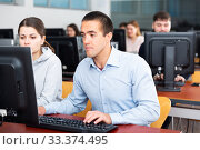Купить «Man and woman study together in university computer class», фото № 33374495, снято 31 марта 2020 г. (c) Яков Филимонов / Фотобанк Лори