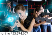 Girl holding laser pistol while playing lasertag game with her f. Стоковое фото, фотограф Яков Филимонов / Фотобанк Лори