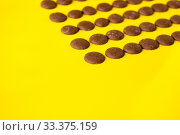Купить «Drops of milk chocolate are laid out in a row on a yellow background», фото № 33375159, снято 14 марта 2020 г. (c) Катерина Белякина / Фотобанк Лори