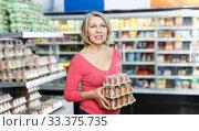 Купить «woman shopping for eggs in food department», фото № 33375735, снято 8 февраля 2019 г. (c) Яков Филимонов / Фотобанк Лори