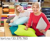 Купить «Two women customers of different ages looking through pillows in textile shop», фото № 33375783, снято 15 февраля 2017 г. (c) Яков Филимонов / Фотобанк Лори
