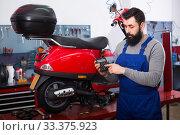 Multi-ethnic guy is preparing bill for motorcycle repair. Стоковое фото, фотограф Яков Филимонов / Фотобанк Лори