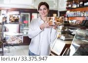 Купить «Seller offering rolled pastry», фото № 33375947, снято 24 января 2017 г. (c) Яков Филимонов / Фотобанк Лори
