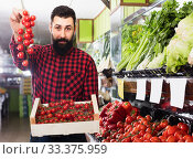 Man seller showing fresh tomatoes in grocery shop. Стоковое фото, фотограф Яков Филимонов / Фотобанк Лори
