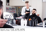 male hairdresser showing resulting haircut to client at hair salon. Стоковое фото, фотограф Яков Филимонов / Фотобанк Лори