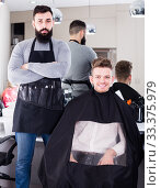 Young guy stylist demonstrating final haircut to positive client at hairdressing salon. Стоковое фото, фотограф Яков Филимонов / Фотобанк Лори